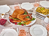 Set table with roast turkey and side dishes