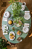 Table set in Mediterranean style with pale green tablecloth