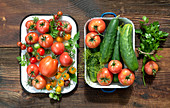 Various fresh tomatoes, cucumbers and herbs in enamel containers