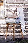 Stapel gefaltete Stoffe auf einem Kaffeehausstuhl vorm alten Holzhaus