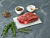 Raw sirloin steak on a piece of paper surrounded by herbs and spices