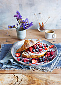 A croissant with cream, lavender cream and fresh berries