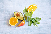 A green smoothie with avocado, spinach, orange and pears
