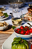 Outdoor table with tomatoes, pasta with cheese and pepper, shrimp skewers, artichokes and white wine