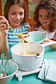 Mädchen nehmen sich Hühnchen-Zuckermais-Ramen