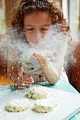 Mädchen bestäubt Kabeljau-Erbsen-Puffer mit Mehl