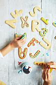 Kinder verzieren Butterplätzchen mit bunten Lebensmittelfarben
