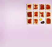 Mehrere Toast mit Marmelade aufgereiht auf rosa Untergrund