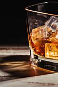 Glas Scotch mit Eiswürfeln auf rustikalem Holztisch