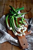 Bunch of ripe scallions placed on wooden cutting board