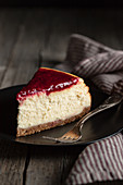 Delicious homemade cheesecake with red berry jam served on black plate on wooden table