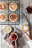 Breakfast at wooden table with cup of cappuccino and fresh homemade buns with berry jam
