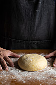 Forming artisan round bread loaf while standing at wooden table dusted with white flour