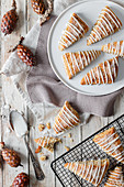 Tasty sweet homemade triangle scones decorated with sugar icing placed on white plate and on metal grid