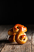 Delicious fresh baked traditional saffron buns with raisin placed on wooden table against black background