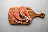 Fresh salmon steaks on wooden board prepared for delicious healthy recipe