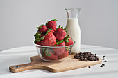Ripe strawberries and heap of chocolate pellets on cutting board near bottle of milk