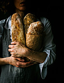 Cropped unrecognizable woman in apron holding ciabatta bread while standing on dark background