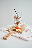 Glass mugs of delicious fresh yoghurt with strawberry, chocolate, banana and tangerine