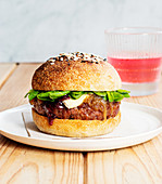 Delicious homemade camembert burger with berry jam placed on wooden table