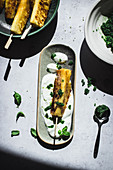 Roasted pineapple served with fresh yogurt and basil sugar on table with shadows