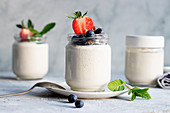 Homemade cashew vegan yogurt served on glass jars on white rustic table