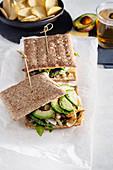 Sandwich mit Avocado, Kartoffelchips und Glas Bier im Café