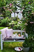 Bank mit Kissen und Tablett unter Rosenbogen im sommerlichen Garten