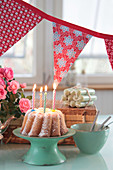 Birthday table with cake with candles, garland and roses
