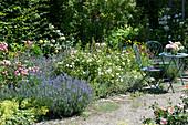 Sitzplatz am Beet mit Rosen, Lavendel, Katzenminze, Frauenmantel und Vexiernelke, kleiner Rosenstrauß als Tischdeko