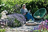 Frau entspannt sich im Garten neben Lavendel und Rosen
