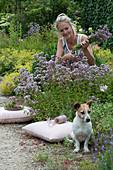 Frau schneidet blühenden Oregano, Hund Zula sitzt am Beet