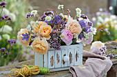 Gesteck mit Rosen, Glockenblumen, Oregano, Witwenblume und Prachtkerze in alter Schublade