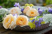 Schale mit gelben Rosenblüten, Glockenblumen, Labkraut und Knorpelmöhre im Wasser