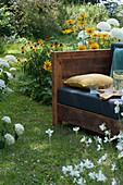 Sofa im Garten zum draußen wohnen im Sommer, umgeben von Sonnenhut und Strauchhortensien