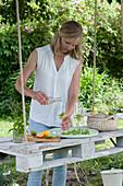 Frau gießt Holunderblütensirup in Gläser mit Minze und Orangenscheibe, hängende Palette als Tisch