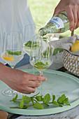 Frau füllt Gläser mit Mineralwasser, frische Minze und Orangenscheibe
