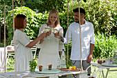 Hängender Tisch aus weiß angemalter Palette, Freunde stoßen an
