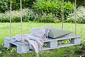 Weiße Palette als Sitzplatz mit Seilen an Baum gehängt, Decke und Kissen