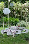 Weiße Palette als Sitzplatz mit Seilen an Baum gehängt, Papierlampions, Krug mit Wasser, Minze und Himbeeren