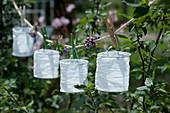 Weiße Papierlampions und Blüten vom Eisenkraut mit Wäscheklammern an Schnur gehängt