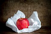 Ein Apfel auf weißem Seidenpapier