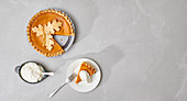 Pumpkin pie, cut and served with cream