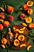 Fresh peaches with leaves on a wooden board