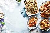 Beilagen zum Osterlunch (grünes Gemüsegratin, Möhren, Bratkartoffeln, Yorkshirepuddings)