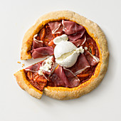 Wholemeal pizza with cured ham and burrata