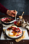 Pancakes with yoghurt baked plums topped with a spoonful of fruit sauce