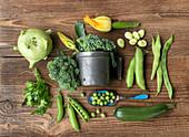 Fresh green garden vegetables on a wooden background