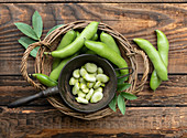 Fresh broad bean pods and peeled beans