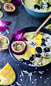 Mango smoothie bowl topped with passion fruit, an orchid, blackberry, yellow kiwi and coconut